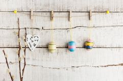 Rustic Easter background: Vintage painted eggs and white heart hang on clothespins against old white wooden wall. Holiday concept royalty free stock photos