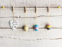 Rustic Easter background: Vintage painted eggs and white heart hang on clothespins against old white wooden wall royalty free stock images