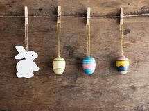 Rustic Easter background: Vintage painted eggs and white heart hang on clothespins against old wooden wall. Holiday concept stock photography
