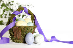 Rustic Easter Basket with Eggs. A rustic basket made of bark and moss filled with colorful speckled eggs Stock Image