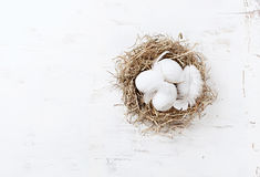 Rustic Easter Nest with White Eggs and feathers Royalty Free Stock Image