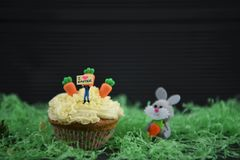 Cupcake topped with a miniature person figurine holding a sign board indicating I love Easter with some decorations. Rustic Easter time decorations with some Stock Photo