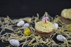 Cupcake topped with a miniature person figurine holding a sign indicating i love Easter with some decorations. Rustic Easter time decorations with some straw and royalty free stock photos