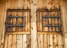 Rustic facade of a wooden house with wooden shutters Royalty Free Stock Photography