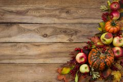 Rustic fall greeting card background with pumpkin, red leaves, apples, viburnum berries royalty free stock photo
