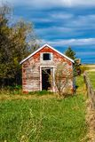 Rustic farm out building under stormy sky. Fading red paint in rural Alberta, Canada Stock Photo