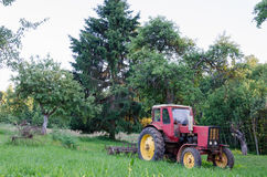Rustic farm tractor in summer garden Royalty Free Stock Image