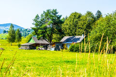 Rustic farm in Ukraine. Well on the hill, firewood in the yard, old house with stable. Agricultural village Kosmach in Carpathian mountains. Trees and hills on Stock Photos