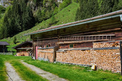 Rustic farming scene. Firewood stacked by the alpine hut Royalty Free Stock Image