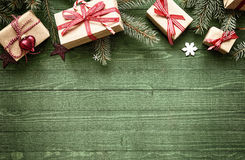 Rustic festive Christmas border. With gift-wrapped presents tied with colorful red ribbon amongst fresh pine foliage across the top of the frame over green wood Royalty Free Stock Photos