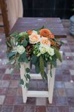 Rustic flower arrangement with beige roses, orange dahlia and a lot of greenery. Table decorated with flowers near the wedding arc. H. Wedding arrangement Stock Photography