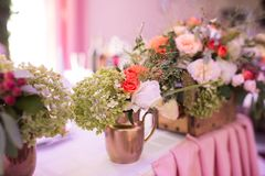 Rustic flower arrangement in a golden vase at a wedding banquet. Table set for an event party. Or wedding reception royalty free stock photography