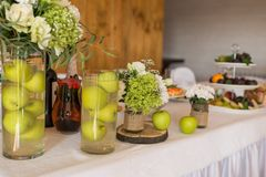 Rustic flower arrangement with white flowers and greenery in a glass vase with water and apples at a wedding banquet. Table set fo. R an event party or wedding stock photo