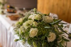 Rustic flower arrangement with white flowers and a lot of greenery close up. Table set for an event party or wedding reception. Roses royalty free stock image