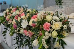 Rustic flower arrangement with white and pink flowers at a wedding banquet. Table set for an event party or wedding reception. Flowers stock photography