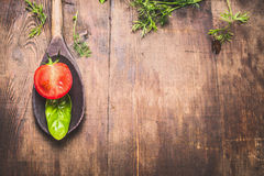 Rustic food background for cooking or recipes with wooden spoon , basil leaf and tomato, top view. Stock Images