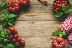 Rustic food background. Heirloom tomatoes and basil on wood royalty free stock photos