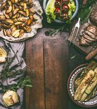 Rustic food background with sliced fried pork meat, baked potatoes around cutting board. On rustic table, top view Royalty Free Stock Images