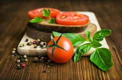Rustic food : sandwiches of rye bread with tomato and basil Stock Photography