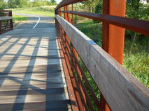 Rustic Foot Bridge. Antique Rustic footbridge over landscaping continues on to biking /  hiking trail Stock Photos