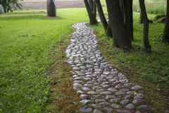 Rustic footpath of natural stone through a park. Rustic footpath of natural stone meandering through lush green grass and trees in a park or garden disappearing royalty free stock image