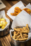 Rustic french fries and other snack food on table Stock Images