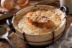 Rustic French Onion Soup. A bowl of delicious rustic french onion soup with toasted baguette and melted swiss cheese stock photo