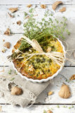 Rustic french quiche with peas and walnuts on baking dish on wooden table with thyme bouquet Stock Photos