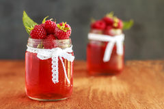 Rustic fresh ripe raspberry jam in glass bottles with leaves on brown background. Copy space. Close up. Front view. Royalty Free Stock Photo
