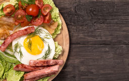 Rustic fried egg with ham and tomatoes top view Royalty Free Stock Photo