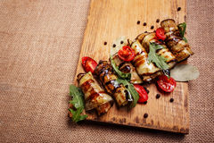 Rustic fried stuffed eggplant on a wooden board. Rustic fried stuffed eggplant with cheese and meat decorated with arugula, tomatoes and sauce on a wooden board Stock Image