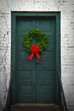 Rustic Front Door Wreath. Rustic green front door of a white brick building hangs a fresh green wreath finished with a big red bow Stock Image