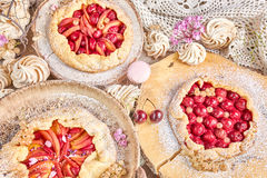 Rustic fruit tarts and meringues, homemade pastry. Royalty Free Stock Photos