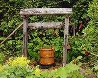 Rustic Garden Well with water Bucket. Traditional Wooden garden well with water Bucket hanging on a rope and hook Royalty Free Stock Image
