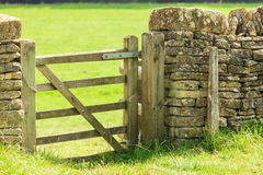 Rustic gate in drystone wall in Bibury England UK. Nature summer landscape. Countryside view and rustic gate in drystone wall in village Bibury England, UK Royalty Free Stock Photography