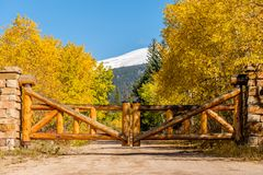 Rustic gate made of logs on unpaved road Royalty Free Stock Image
