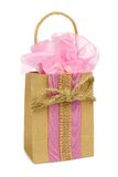 Rustic gift bag with pink tissue, twine bow over white Royalty Free Stock Photography