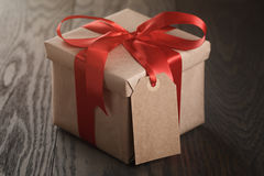 Rustic gift box with red ribbon bow and emmpty tag. On old wood table Stock Photography