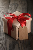 Rustic gift box with red ribbon bow and empty tag Royalty Free Stock Photo