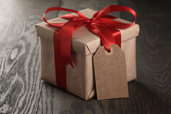 Rustic gift box with red ribbon bow and empty tag. On old wood table Royalty Free Stock Photography