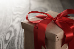 Rustic gift box with red ribbon bow Royalty Free Stock Photos