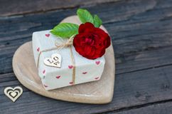 Rustic gift box with roses and hearts, on old wood table. With copy space Stock Photo