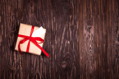 Rustic gift with a red ribbon on  wooden background Royalty Free Stock Image