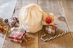 Rustic gift sack with candy canes and pine cones on wooden surfa Royalty Free Stock Photo