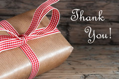 Rustic Gift with Thank You. Rustic Gift with red white Ribbon on Wood and the Words Thank You Stock Photo