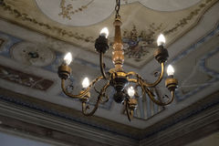 Rustic gilt chandelier against a painted ceiling Stock Photo