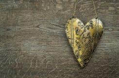 Rustic golden heart ornament on vintage wooden background. Rustic metal golden heart ornament on vintage wooden background Stock Photos