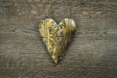 Rustic golden heart ornament on vintage wooden background Royalty Free Stock Images