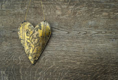 Rustic golden heart ornament on vintage wooden background Stock Images