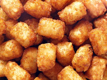Rustic golden potato tater tots food background. Close up of rustic golden potato tater tots food background Royalty Free Stock Images